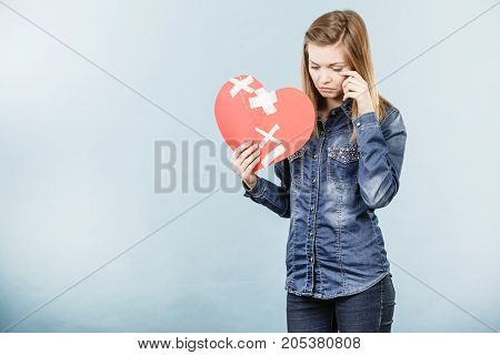 Sad young teenage woman with broken heart made of paper. Negative sad emotions relationship problems concept. Shot on blue.