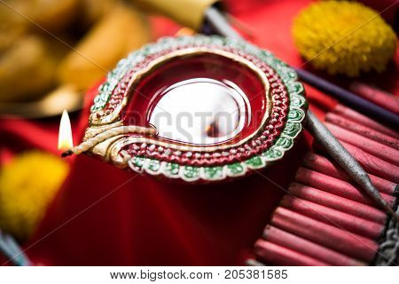 stock photo showing Diwali still life with Diya or oil Lamp and fire crackers like rocket fulzadi, anar and chakri, selective focus