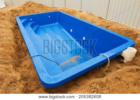 Installation plastic fiberglass pool in the ground at house backyard. Construction site