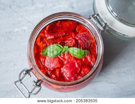 Sun dried tomatoes with basil in a glass jar on a concrete table. Traditional recipes of the Mediterranean cuisine. Vegetarian concept
