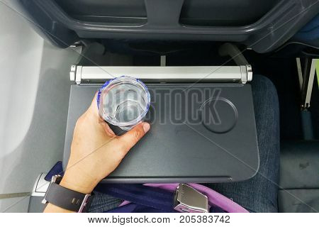 Hand Holding Disposable Mineral Water On Table In Air Plane
