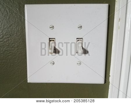 a white light switch on green wall with switches set to off
