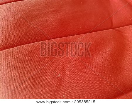 a smooth red fabric and some peices of lint