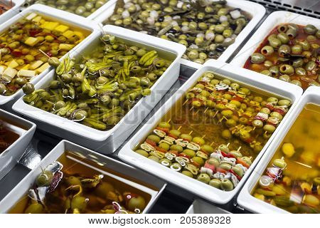 mixed olive tapas snacks in la boqueria market display trays in barcelona spain