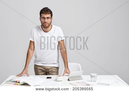 Convinced Bearded Man In Casual Clothes, Stands Near Desk With Gadgets. Male Enterpreneur Waits For