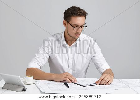 Serious Businessman Looks At Diary, Decides When To Arrange Meeting, Sits In Office, Work With Moder
