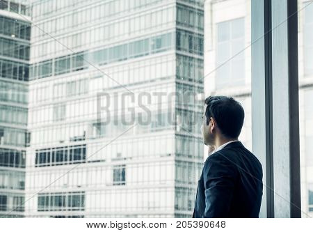 Businessman using mobile phone near office window at office buildingcommunication conceptvintage filter.
