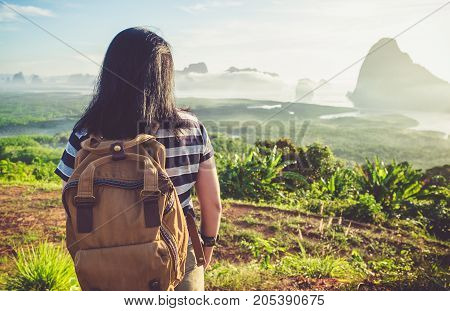 Happy young traveler woman backpacker looking backward to camera with a beautiful of nature at top of mountain view point and seaFreedom wanderlustKhao Samed Nang Chee ViewpointPhang NgaThailand