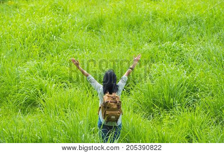 Happy young traveler woman backpacker raised arm up to sky enjoying a beautiful of nature at grass field greenery fresh airFreedom wanderlust concept.