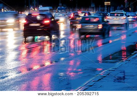 Cars Driving On Wet Road With Headlights