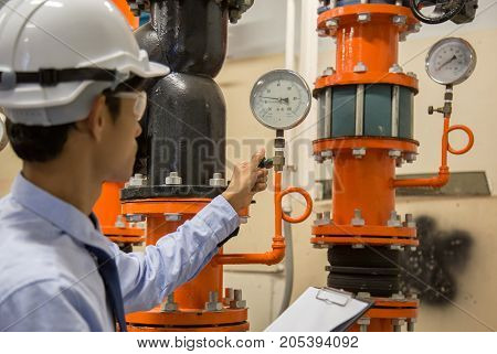 Engineer checking Condenser Water pump and pressure gauge chiller water pump with pressure gauge.