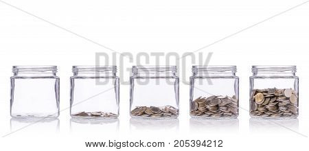 Thai Coin (baht) In Clear Glass Jar With Different Level From Less To More. Studio Shot Isolated On