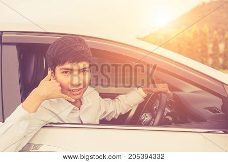 Young Businessman Sitting In The Modern Car And Showing Hand With Call Symbol. For Car Rent Or Car B