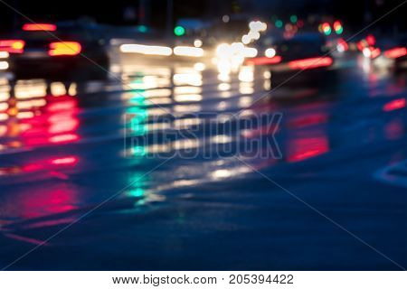 Blurry Image Of Cars Driving On Wet Road In City With Headlights Switched On