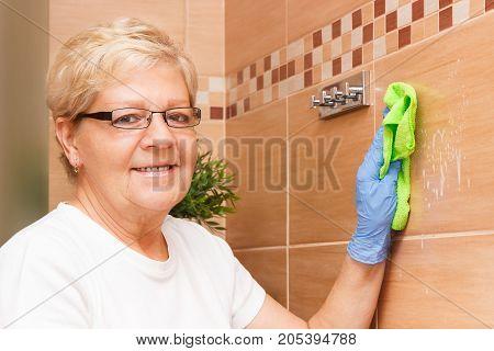 Elderly Senior Woman Cleaning Bathroom Tiles Using Green Microfiber Cloth, Household Duties Concept