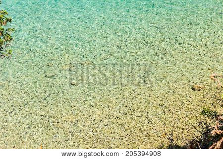 Seafloor is visible through turquoise transparent water view above.