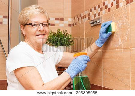Senior Woman Washing And Cleaning Bathroom Tiles Using Sponge And Detergent, Concept Of Household Du