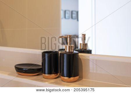 Black ceramic toiletries bathroom accessories at the glass.