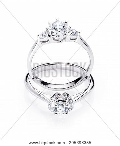 two diamond engagement wedding rings on isolated white background with light reflection one ring standing up one ring laying down
