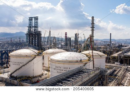 Oil Refinery Construction Site View With Cranes And Various Equipment Under Dramatic Sky