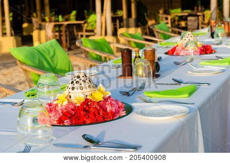 Table setting for wedding reception with red and yellow flowers