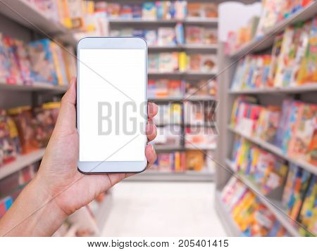 Hand holding smart phone with blur bookstore background.
