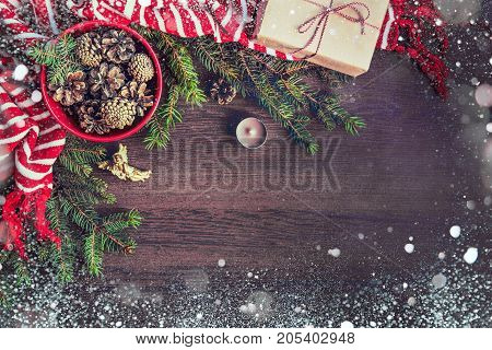 Top view of christmas decoration - red bowl full of fir-cones gift box wrapped in kraft paper golden angel pine branches candle and red and white striped winter scarf. Christmas theme. Dark wooden background. Snow frame.