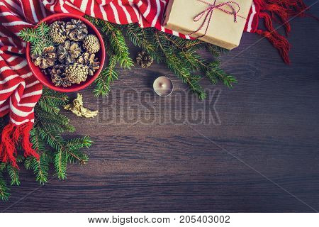 Top view of christmas decoration - red bowl full of fir-cones gift box wrapped in kraft paper golden angel pine branches candle and red and white striped winter scarf. Christmas theme. Dark wooden background.