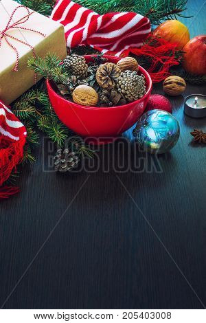 Christmas decoration - red bowl full of fir-cones gift box wrapped in kraft paper pine branches candle nuts anise apples christmas toys and red and white striped winter scarf. Christmas theme. Dark wooden background.Copy space