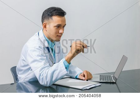 Asian young doctor using laptop computer for looking at patient information and pointer with pen at hospital isolated on gray background concept of medical technology innovation.