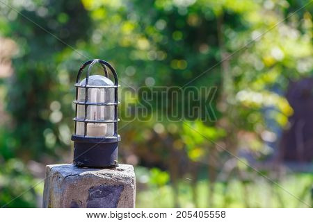 Light bulb on concrete pole with green bokeh background.