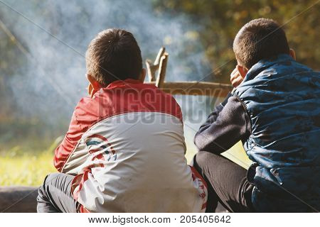 Two boys teenagers in camping seat near campfire, horizontal