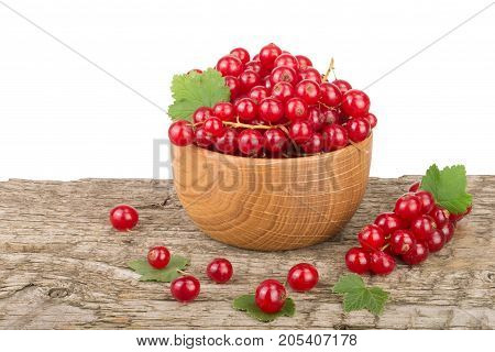 Red currant berries in wooden bowl with leaf on wooden table with white background.