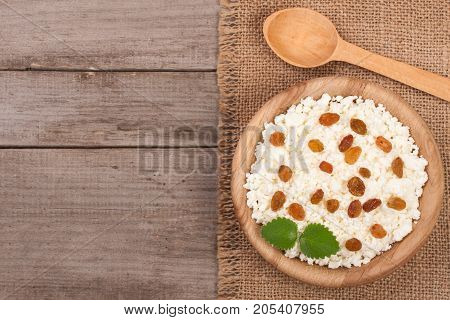 Cottage cheese with raisins in a wooden bowl on old wooden background with copy space for your text. Top view.