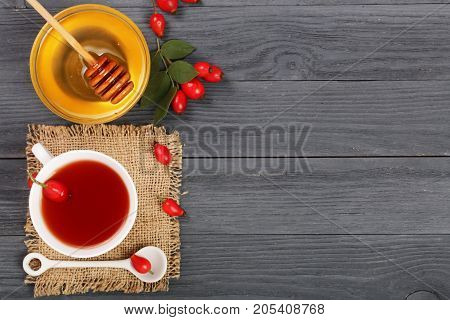 tea with rose hips and honey on a black wooden background with copy space for your text. Top view.