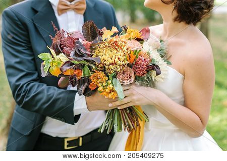 autumn, occasion, love concept. fiance dressed in magnificent black suit and creamy bow tie and his bride with delicate shoulders holding togethere wedding bouquet of fall shades