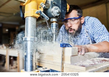 Portrait of bearded carpenter blowing sawdust off wooden furniture part while using drilling machine in work shop