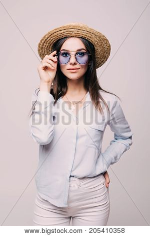 Young Girl Posing In Hat And Glasses In The Whit Wall
