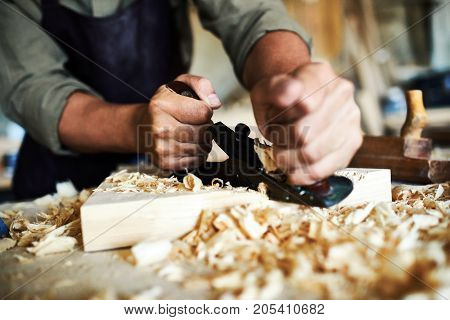 Closeup portrait of strong male hands shaving piece of wood with plane tool in carpenters workshop making furniture