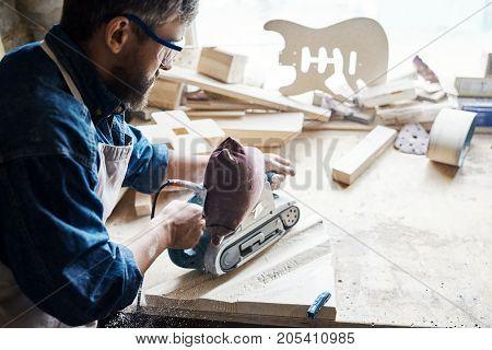 Back view portrait of skilled craftsman sanding piece of wood in carpenters workshop against window