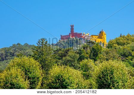 Aerial view of colorful Pena Palace on top of a hill above Sintra in sunny day, blue sky. Panorama of Palacio da Pena, a National Monument, Unesco Heritage and one of Seven Wonders of Portugal.