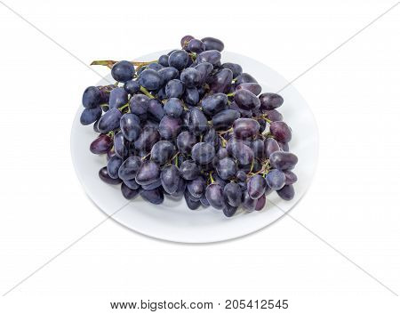 Big cluster of the ripe dark blue table grapes on a white dish aon a white background