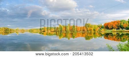 Panorama of the autumn forest and park on the shore of the lake reflection of trees and sky with clouds in calm surface of the water