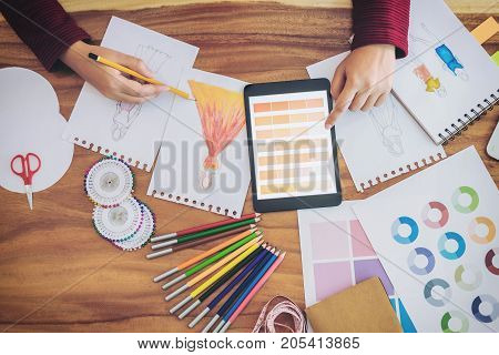 Young woman designer working as fashion designers at work with fashion sketches and color charts profession and job occupation Fashion Designer Stylish Concept.
