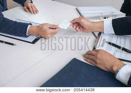 Interviewer or Board reading a resume during job interview Employer interviewing a young male job seeker for recruitment talking in modern office and filing card employment and recruitment concept.