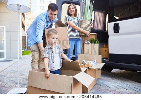Portrait of happy young family with little son loading cardboard boxes into moving van outdoors