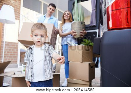 Portrait of cute little boy looking at camera with his parents holding cardboard boxes in background outdoors