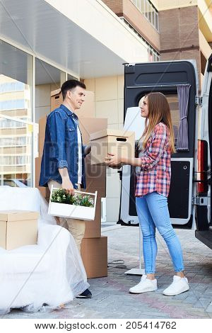 Side view portrait of young happy woman unloading boxes from moving van handing them to smiling husband