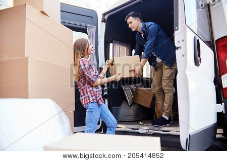 Portrait of young  man loading cardboard boxes to moving van with smiling wife helping him