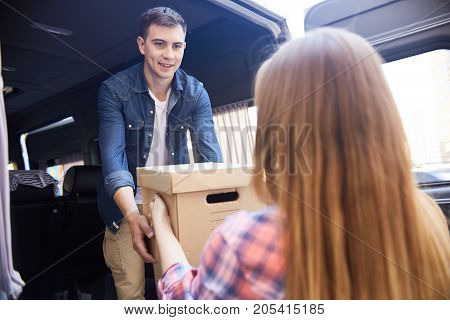 Portrait of happy young man taking cardboard boxes from his wife and loading them into moving van